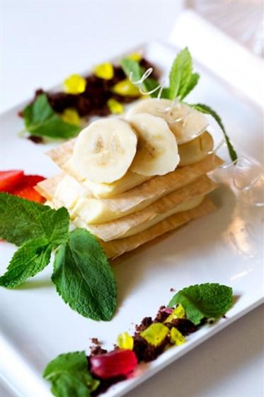 Ресторан Graf-in - фотография 30 - Оригинальный десерт из тонкого хрустящего теста фило с легким кремом маракуйя и ломтиками свежей клубники и банана