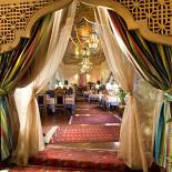 Ресторан Узбекистан - фотография 3 - При входе гостей встречают тяжелые резные деревянные двери и факела – обязательный элемент восточного дворца, кроме освещения, по восточным легендам, они являются символичными: это хранители домашнего очага. Материалом для орнамента решеток является особо долговечный и дорогой сорт дерева. Это «живой» материал: он не обрабатывался и не покрывался лаком - дерево «дышит». Каждый элемент вытачивался и собирался вручную без единого гвоздя, при этом прочность такого изделия измеряется столетиями. Это авторская, неповторимая и уникальная работа.